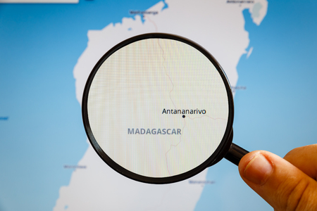Antananarivo, Madagascar. Political map. The city on the monitor screen through a magnifying glass in hand.