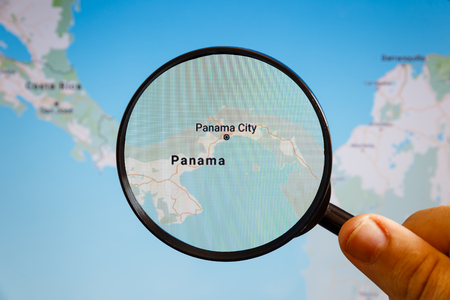 Panama City, Panama. Political map. The city on the monitor screen through a magnifying glass in hand.