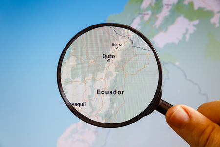 Quito, Ecuador. Political map. The city on the monitor screen through a magnifying glass in hand.