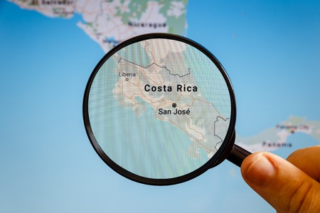 San Jose, Costa Rica. Political map. The city on the monitor screen through a magnifying glass in hand.