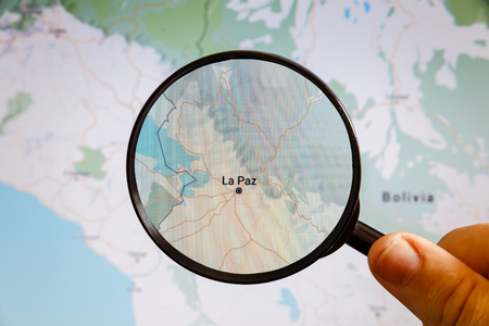 La Paz, Bolivia. Political map. The city on the monitor screen through a magnifying glass in hand.