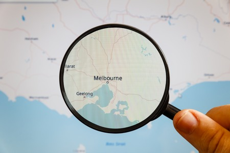 Melbourne, Australia. Political map. The city on the monitor screen through a magnifying glass in hand. Stockfoto