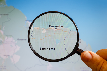 Paramaribo, Suriname. Political map. The city on the monitor screen through a magnifying glass in hand. Stockfoto