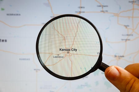 Kansas City, United States. Political map. The city on the monitor screen through a magnifying glass in hand.