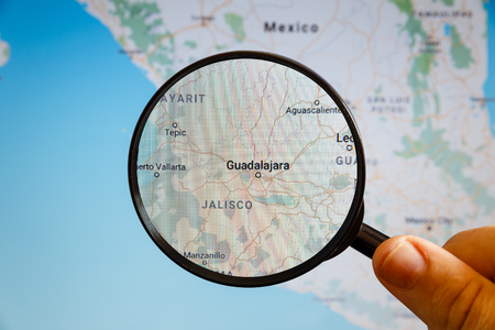 Guadalajara, Mexico. Political map. The city on the monitor screen through a magnifying glass in hand.