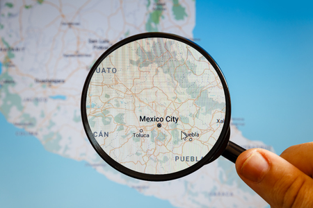 Mexico City, Mexico. Political map. The city on the monitor screen through a magnifying glass in hand.
