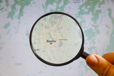 Brasilia, Brazil. Political map. The city on the monitor screen through a magnifying glass in hand.