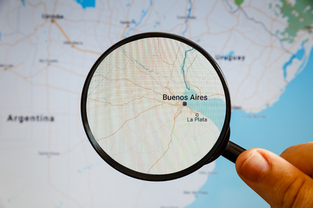 Buenos Aires, Argentina. Political map. The city on the monitor screen through a magnifying glass in hand.