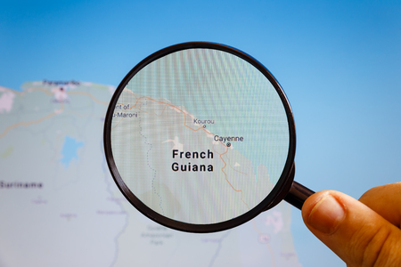 Cayenne, French Guiana. Political map. The city on the monitor screen through a magnifying glass in hand.
