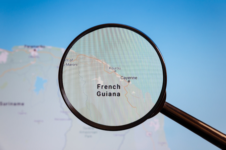 Cayenne, French Guiana. Political map. The city on the monitor screen through a magnifying glass.