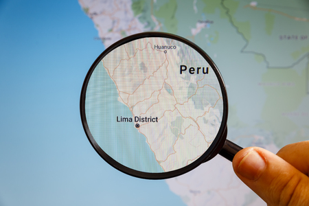 Lima, Peru. Political map. The city on the monitor screen through a magnifying glass in hand.