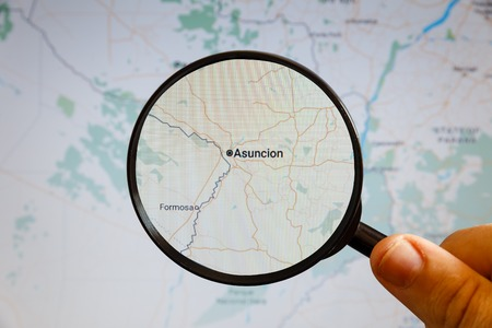 Asuncion, Paraguay. Political map. The city on the monitor screen through a magnifying glass in hand. Stockfoto