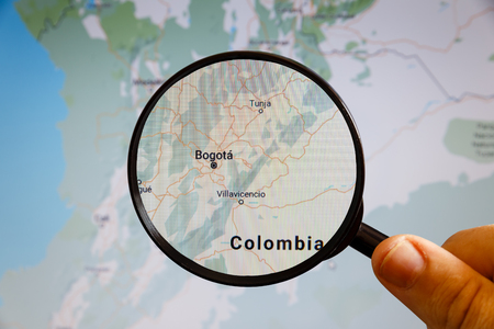 Bogota, Colombia. Political map. The city on the monitor screen through a magnifying glass in hand.