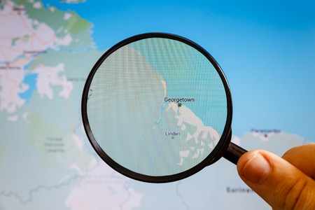 Georgetown, Guyana. Political map. The city on the monitor screen through a magnifying glass in hand. Stockfoto