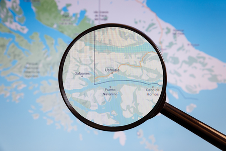 Ushuaia, Argentina. Political map. The city on the monitor screen through a magnifying glass.