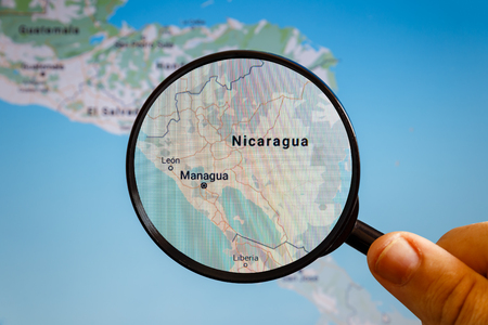 Managua, Nicaragua. Political map. The city on the monitor screen through a magnifying glass in hand. Stockfoto