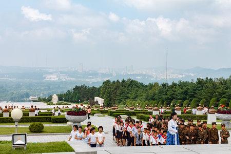 Pyongyang, North Korea - July 27, 2014: Korean schoolchildren and soldiers at the memorial cemetery of revolutionaries in Pyongyang.