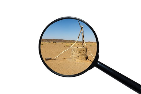 water well in Sahara desert, view through a magnifying glass, white background