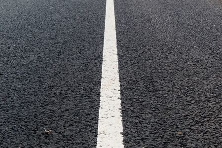 Linea continua bianca. Segnaletica stradale su strada asfaltata.