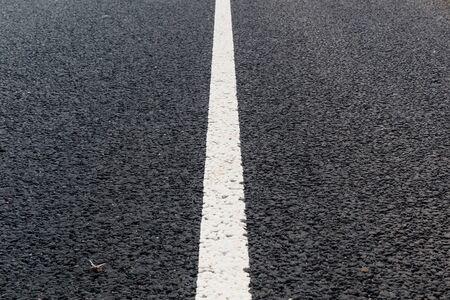 White solid line. Road marking on an asphalt road.