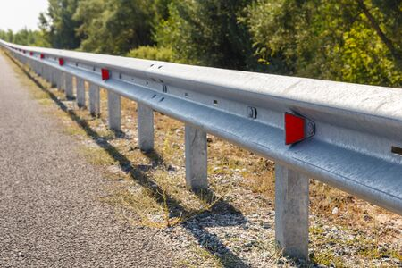 red road reflectors along the road. metal road fencing of barrier type, close-up. Road and traffic safety