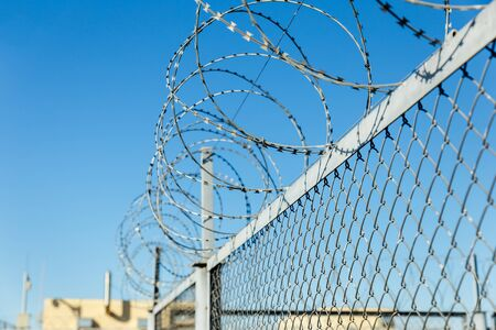 fence with barbed wire, barbed wire on a wire mesh fence