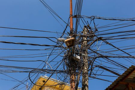 The chaos of cables and wires in Kathmandu, electric and telephone wires wound on a lamppost. Nepal