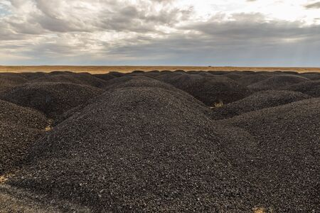 large piles of old asphalt in the steppe after road repair, Kazakhstan