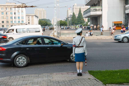Pyongyang, North Korea - July 29, 2014: A girl policeman regulates traffic at a crossroads in Pyongyang. One of the symbols of Pyongyang.