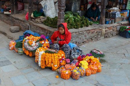 Kathmandu, Nepal - November 25, 2016: Nepalese woman sells flower wreaths at Kathmandu street.