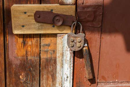 Vintage mechanical combination lock hanging on door. The door of the house is locked.