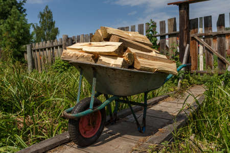 A garden cart with chopped wood stands on a wooden bridge.