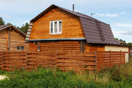 New country house, bathhouse. Country wooden house in the village with a fence.