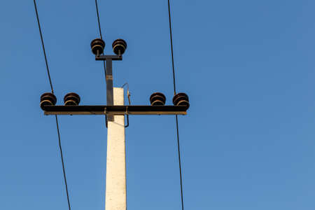 High voltage power line. Electric power line support and wires against the blue sky.
