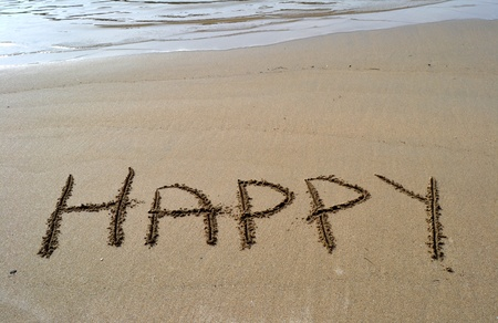 Beach with the word happy written in the sand photo