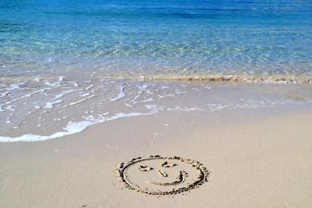 浜の砂に書かれた顔を笑顔します。 写真素材