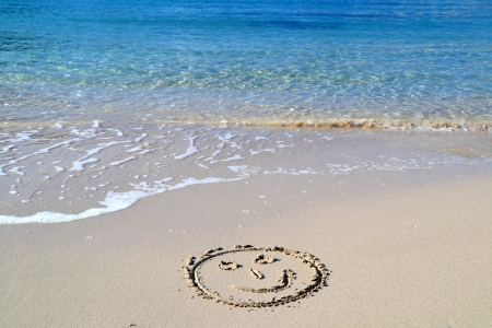 Smile face written in the sand in the beach Imagens