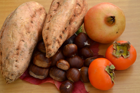 sweet potatoes: Typical autumn food with chestnuts, sweet potatoes, pomegranate and persimmons Stock Photo