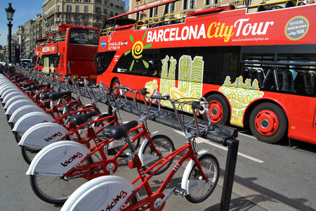 BARCELONA, SPAIN - OCTOBER 23  Bikes and Tourist Bus in Barcelona, Spain on October 23, 2013  The bike rental service and Barcelona City Tour Bus are two ways to discover the city Stock Photo - 25577981