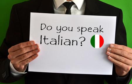 Businessman showing a sheet with text Do you speak Italian Standard-Bild