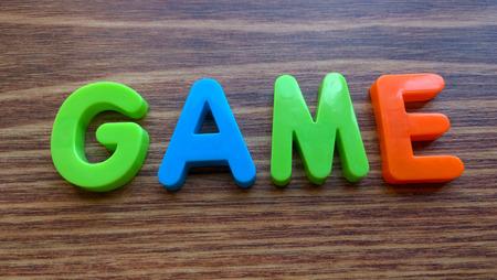 word game: The word Game made with colorful letters on a wooden background