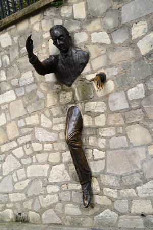 novelist: PARIS, FRANCE - OCTOBER 19: Sculpture called Le Passe-Muraille in Paris, France on October 19, 2013. It is a tribute to the French novelist Marcel Ayme and represents a man that can walk through walls
