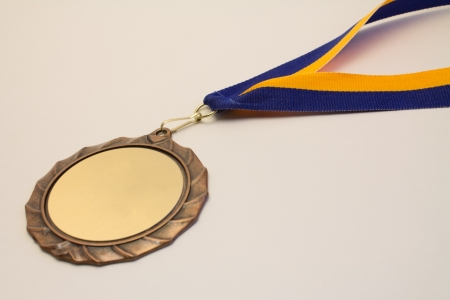A bronze medal with a blue and gold ribbon and a blank medallion