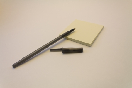 A black pen and its cap with a pad of yellow sticky notes against a white background