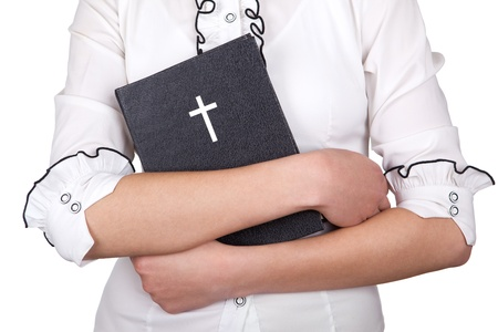 A young girl holding a bible in her hands Standard-Bild