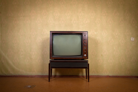 Retro TV on a background of vintage wallpaper in old room with vignetting