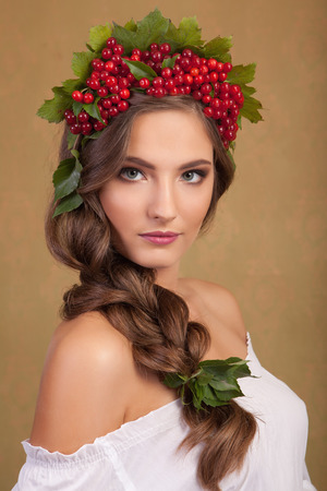 Creative makeup. Young beautiful girl with make-up with a berry and a leaf on yellow background. photo