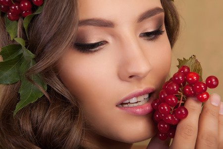 Creative makeup. Young beautiful girl with make-up with a berry and a leaf on yellow background. Archivio Fotografico