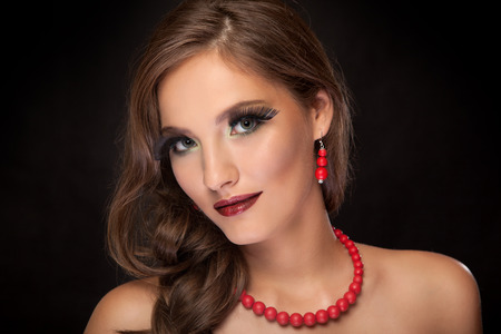 Creative makeup. Young beautiful girl with make-up on black background. photo