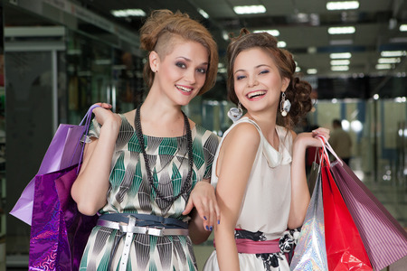 Shopping young beautiful happy girls with colored bags photo